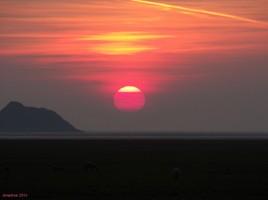 soleil rouge sur Tombelaine , le mont à côté du Mont..