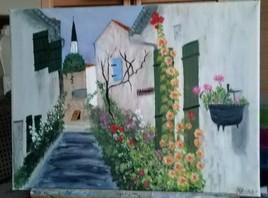 Ruelle avec ses maisons fleuries de roses trémières sur l'Ile de Ré