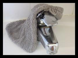 Le regard indiscret du robinet sous le gant de toilette